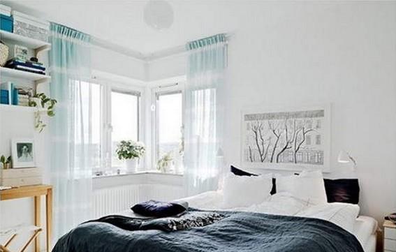 整个卧室采用了极致简约的白色,在这个简约风格图片中,带给我们的是一种浪漫天堂的感觉。转角的地方呗主人做成了窗户的款式,这样一个锐角做成的窗户相互映射,卧室被光线照射的光芒四射。淡淡的蓝色窗帘很是梦幻,而这个卧室背景墙则是用以小幅艺术画来装点,树叶枯萎,枝干努力生长的意境激励了我们的心境。