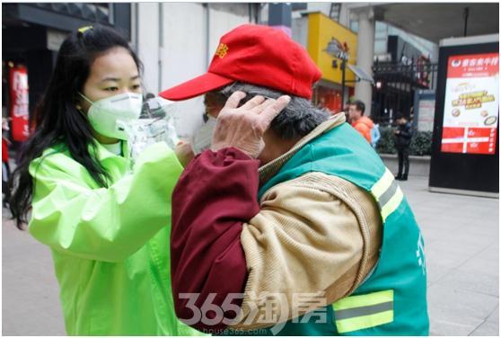 汇得行防霾小分队成员为环卫工派送口罩